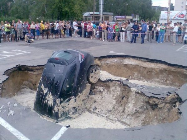 russia parking lot car fall into a crater 600x450